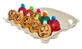 Easter eggs, hand-painted with smiling and terrified cartoon fac. Es. Decorated eggs with funny colorful hairstyles put in a cardboard box, container for eggs Stock Image