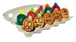 Easter eggs, hand-painted with smiling and terrified cartoon fac. Es. Decorated eggs with funny colorful hairstyles put in a cardboard box, container for eggs Royalty Free Stock Photo