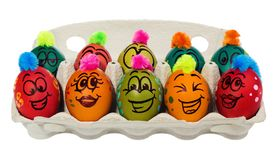 Easter eggs, hand-painted with smiling and terrified cartoon fac. Es. Decorated eggs with funny colorful hairstyles put in a cardboard box, container for eggs Royalty Free Stock Image