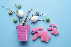 Top view of Easter eggs and handmade rabbits with spring twigs on a pastel blue background. Easter eggs and handmade rabbits with spring twigs and flowers on a Royalty Free Stock Photo