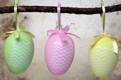 Easter eggs, hanging from a branch. Three decorative Easter eggs hanging from a branch, with calm brown background Stock Images