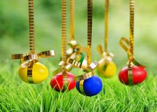 Easter eggs hanging on golden ribbons stock images