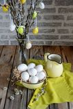 Easter eggs hanging from willow branches with white eggs in yellow plate on the wooden table stock photography