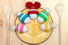 Easter eggs in a hat on a plate. Wooden background top view. Royalty Free Stock Image