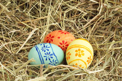 Easter eggs on hay. Three colored Easter eggs on hay at sunny day Royalty Free Stock Images