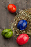 Easter eggs in hay nest on dark wood royalty free stock photography