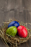 Easter eggs in hay nest on dark wood royalty free stock images