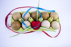 Easter eggs with hearts in a tray on a white background with free space to fill stock images