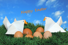 Easter eggs and hens on the grass with sky background. Genuine eggs and origami hens on a small lawn with text 'Happy Easter' in the sky Stock Photography