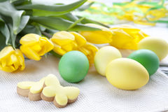 Easter eggs, homemade cookies and yellow tulips over light background with copy space Royalty Free Stock Images