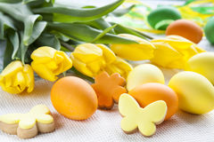Easter eggs, homemade cookies and yellow tulips over light background with copy space Royalty Free Stock Image