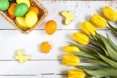 Easter eggs, homemade cookies and yellow tulips over light background with copy space Stock Photo