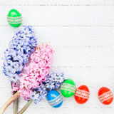 Easter eggs and hyacinths flowers on white tablecloth. Top view Royalty Free Stock Photo