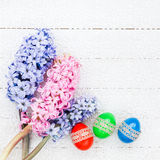 Easter eggs and hyacinths on white tablecloth. Copy space Stock Images