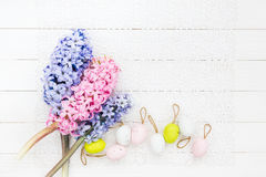Easter eggs and hyacinths on white tablecloth. Top view, copy space Stock Photos