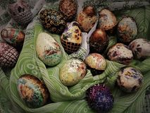 Easter eggs, ilustration. The cheerful eggs are painted in vibrant colors: yellow, gold, copper, red, green, silver. Eggs have different patterns lance, pansies Stock Photos
