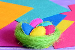 Easter Eggs In A Nest Decoration. Handmade Felt Easter Eggs Set In A Green Sisal Nest Isolated On Colorful Felt Background Royalty Free Stock Photo