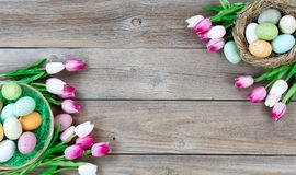 Easter eggs inside basket and bird nest with tulips on lower lef. Traditional basket and bird nest filled with colorful eggs and pink tulips in both corners on Royalty Free Stock Photo