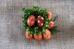 Easter Eggs on jute painted with crayons and onion shall. Easter Eggs on jute. Painting with crayons and onion shall. Homemade pattern. Eggs in basket Royalty Free Stock Photography
