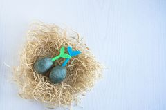 Easter eggs lie in a nest on a white wooden background. Blue and green tails stick out of eggs. View from above. Easter eggs lie in a nest on a white wooden stock images
