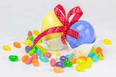 Easter eggs in little nest decorated with a ribbon and jelly belly. Easter eggs in little nest decorated with red ribbon and jelly belly Royalty Free Stock Photography