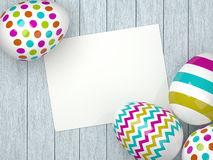 Easter eggs lying on wooden desk with chit Stock Photography