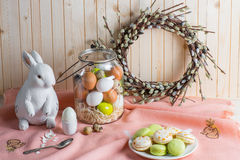 Easter eggs and macarons. Colorful Easter eggs in jar, tasty macarons, catkins wreath and bunny on table Stock Photos