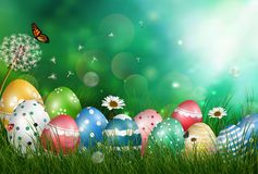Easter eggs in meadow with sun rays on green background Stock Photo
