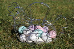 Easter eggs. A metal basket with  Easter eggs pastel colors, white, pink, purple  and green in the garden, in the grass a sunny day Stock Photos