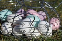 Easter eggs. A metal basket with  Easter eggs pastel colors, white, pink, purple  and green in the garden a sunny day Royalty Free Stock Photos