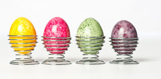 Easter eggs. Multicolored chicken eggs in egg holder. Green, red, yellow, purple egg in metal eggs holder Stock Photos