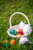 Easter eggs and mums in wicker basket Royalty Free Stock Images