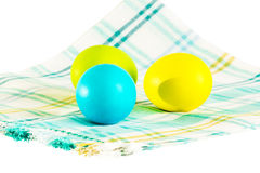 Easter eggs on a napkin on a white background. Three painted Easter eggs on a checkered napkin on a white background royalty free stock photography