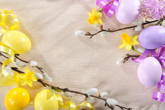 Easter eggs. Narcissus and pussy willow on tablecloth with copy space Stock Image