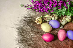 Easter eggs near the bouquet of wild flowers and dried buds of roses. Brightly colored Easter eggs near the bouquet of wild flowers and dried buds of roses on a Royalty Free Stock Photography