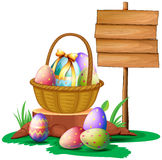 Easter eggs near a wooden signboard Stock Photos