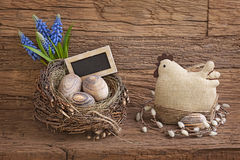 Easter eggs in nest. And flowers on wooden background royalty free stock photography