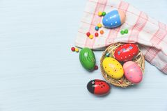 Easter eggs in the nest basket on fabric cloth white table background stock image