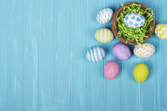 Easter eggs in nest on blue background Stock Photos