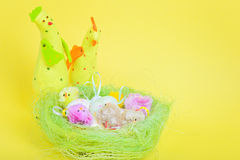 Easter eggs in nest and chickens Stock Photo
