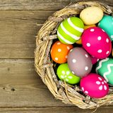 Easter eggs in nest close up on wood Stock Photo