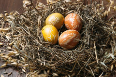Easter eggs in nest on color wooden background Royalty Free Stock Images