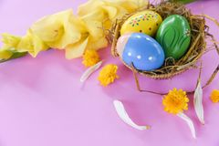 Easter eggs in nest decoration with Gladiolus flowers yellow petal on pink. Background stock photo