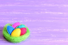 Easter eggs in a nest. Felt Easter eggs set in a green sisal nest isolated on purple wooden background with copyspace for text stock photo