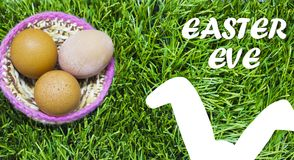 Easter eggs in nest on grass with text: Easter eve. royalty free stock photos