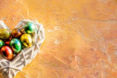 Easter eggs in nest over wooden background. Top View with copy space.easter nest with colored eggs on yellow background royalty free stock images