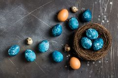 Easter eggs in nest painted by hand in blue color on dark background. Chicken and quail eggs catholic and orthodox easter holiday royalty free stock photography