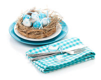 Easter eggs nest on plate with silverware Stock Photography