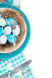 Easter eggs nest on plate with silverware Stock Image