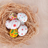 Easter eggs in nest on rustic wooden planks Stock Images